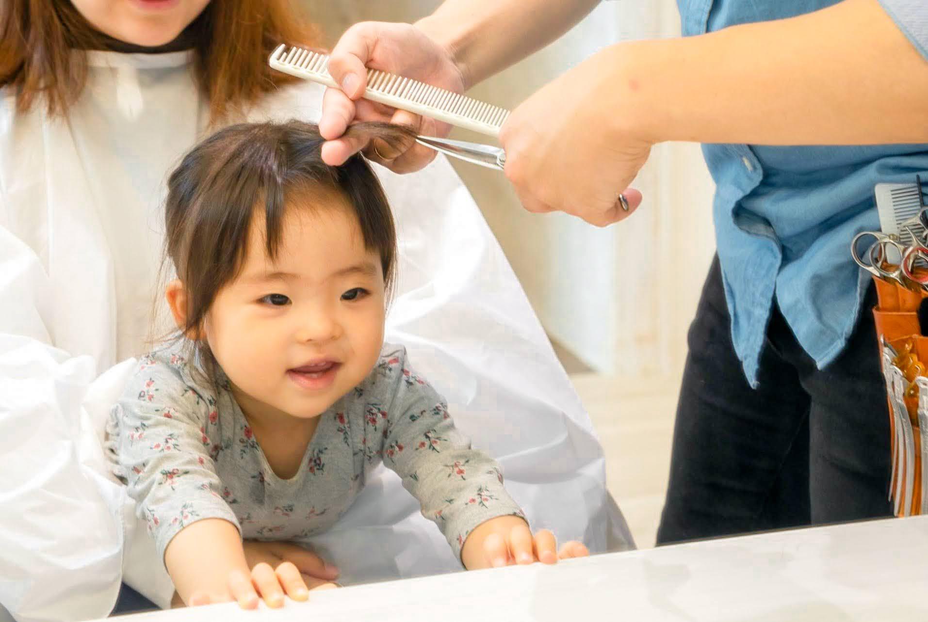 ママに抱っこされている子供の前髪をカット